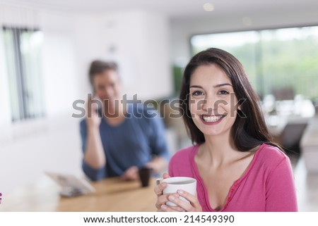 couple at home woman at foreground drinking coffee
