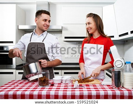 Couple at kitchen cooking together - stock photo