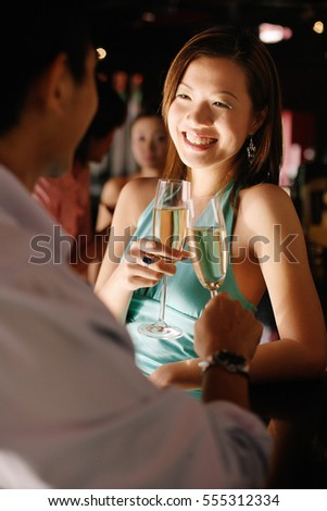 Couple at night club, toasting with champagne glasses