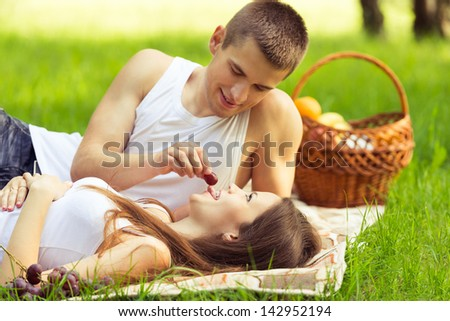 couple at picnic in park. man feeding woman grapes - stock photo