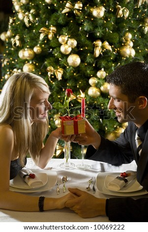 Couple at restaurant on dinner party. They giving each other a present.