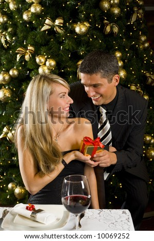 Couple at restaurant on dinner party. They giving each other a present. Front view. - stock photo