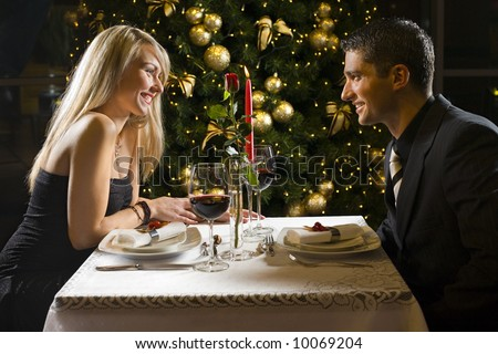 Couple at restaurant on dinner party. They're looking at each other and smiling.