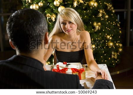 Couple at restaurant on dinner party. They're looking at each other. Focused on her. - stock photo