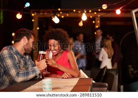 Couple at rooftop party - stock photo