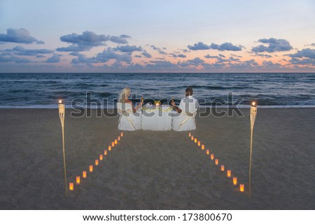 Couple at sea beach during luxury romantic dinner, decorated with candles road and torches flame against beautiful sunset - stock photo
