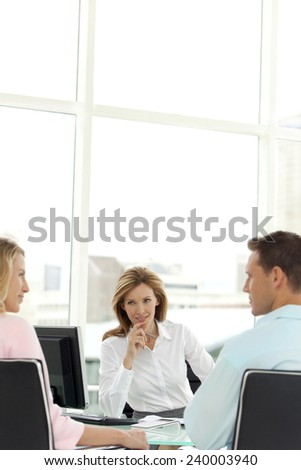 Couple at the bank with financial adviser - stock photo