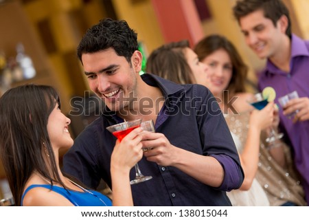 Couple at the bar having drinks and looking very happy - stock photo