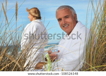 Couple at the beach in robes - stock photo