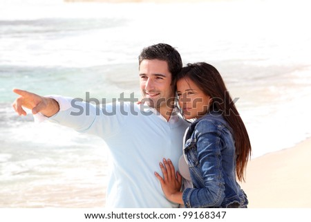 Couple at the beach, man showing something to girl