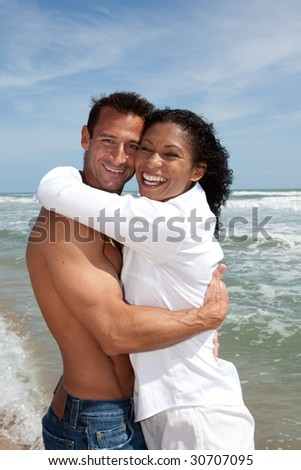 Couple at the beach smiling, having fun