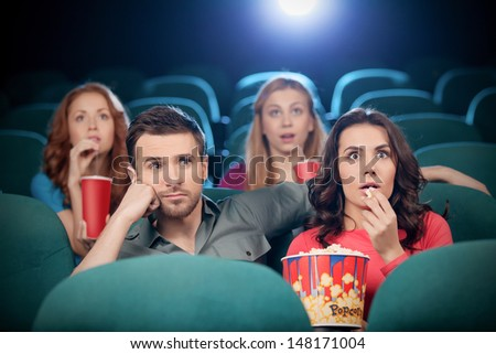 Couple at the cinema. Bored men and excited women watching movie at the cinema