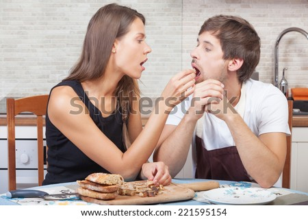 Couple at the kitchen feeding each other with toast - stock photo
