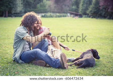 couple at the park / beautiful couple at the park play photo with dog