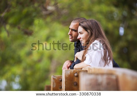 Couple at the park looking away - stock photo