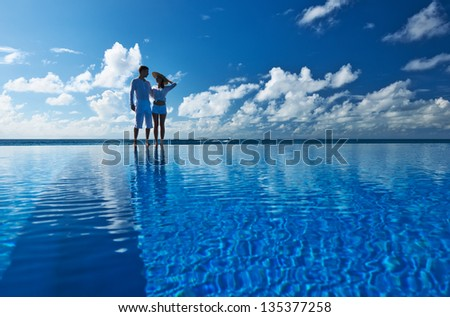 Couple at the poolside against sky - stock photo