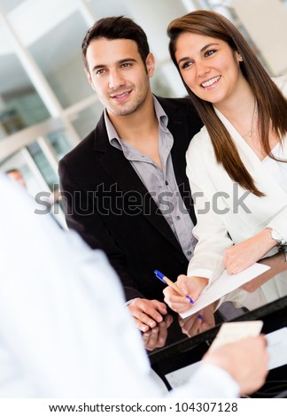 Couple at the reception of a hotel smiling - stock photo