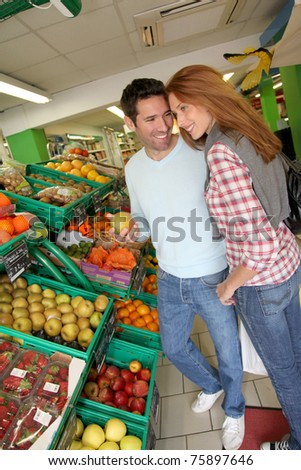 Couple at the supermarket doing grocery shopping - stock photo