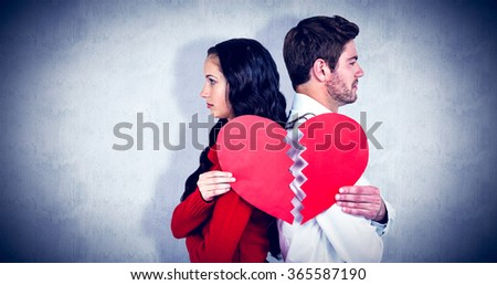 Couple back to back holding heart halves against white background - stock photo