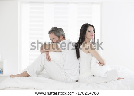 couple back to back in bed - stock photo