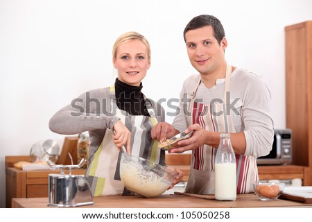 Couple baking in kitchen - stock photo
