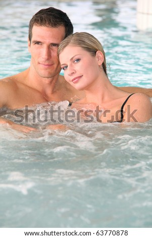 Couple bathing in jacuzzi of spa center - stock photo
