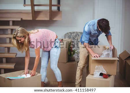 Couple bending and unpacking boxes at new house