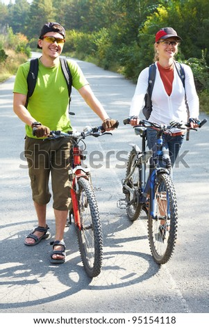 Couple  bicycler  walking with bikes from park - stock photo