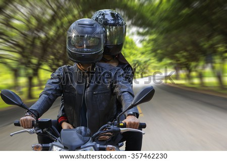 couple biker riding motorcycle in tree tunnel road - stock photo