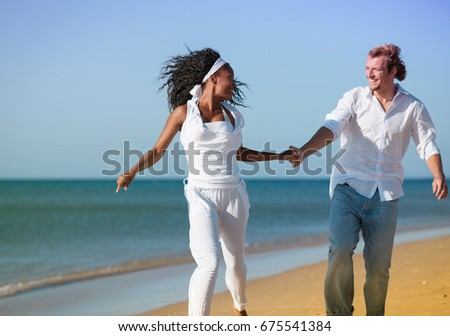 Couple - black woman and Caucasian man - walking and running down a beach in their vacation