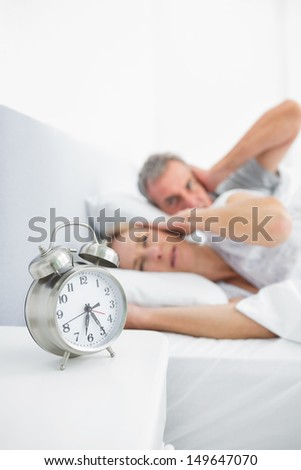 Couple blocking their ears from alarm clock noise in bedroom at home - stock photo