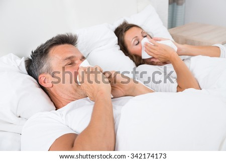 Couple Blowing Their Nose While Sleeping In Bed