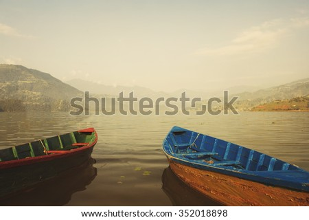 Couple boat on mountain lake. Morning fog, tranquil and calm - stock photo