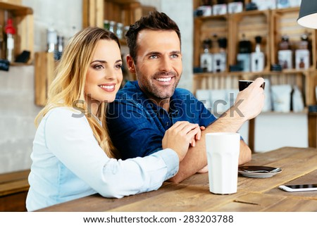 Couple bonding at cafe sitting at bar - stock photo