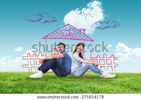 Couple both sitting on floor against blue sky over green field - stock photo