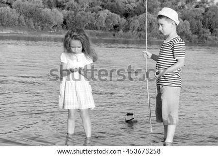 couple,boy and girl on the river summer day.Black and white photo stylized vintage style - stock photo