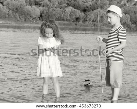 couple,boy and girl on the river summer day.Black and white toned photo stylized vintage style - stock photo