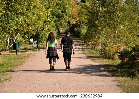 Couple brisk walking in dusty road - stock photo