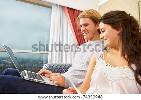 Couple browsing internet at home enjoying their free time