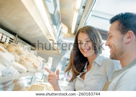 Couple browsing the cheese aisle - stock photo