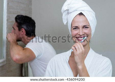 Couple brushing their teeth in the bathroom at home - stock photo