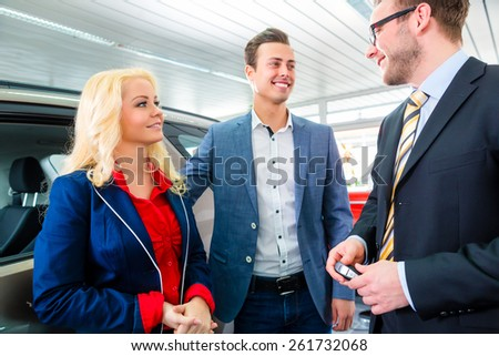 Couple buying car at dealership and consulting salesman - stock photo