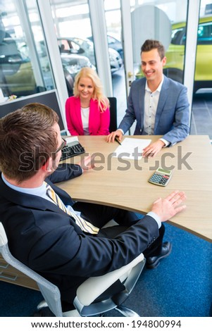Couple buying car at dealership and negotiating price with salesman - stock photo