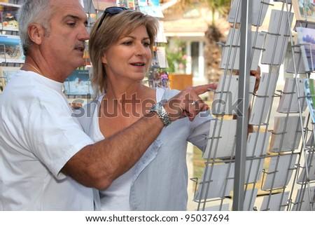 Couple buying postcards - stock photo
