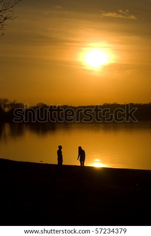 Couple by the lake at sunset - stock photo