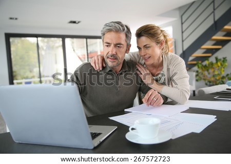 Couple calculating financial savings on internet