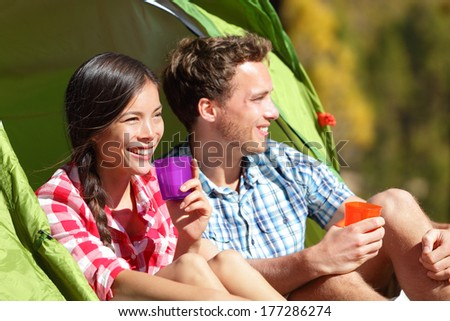 Couple camping drinking water in tent smiling happy outdoors in forest enjoying sun at looking at view. Happy multiracial couple relaxing after outdoor activity hiking. Asian woman, Caucasian man. - stock photo