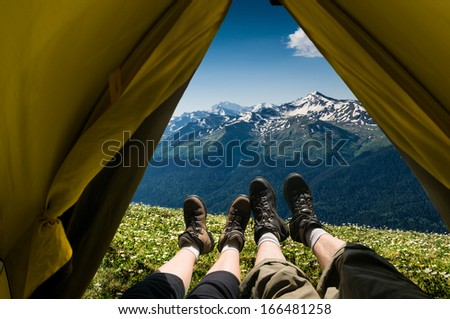 couple camping in mountains - stock photo