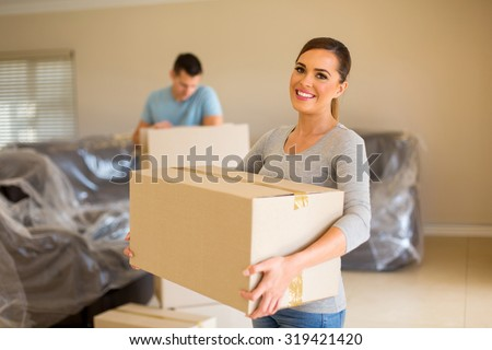couple carrying boxes moving in new house - stock photo
