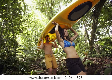 Couple Carrying Kayak in Wilderness Area - stock photo